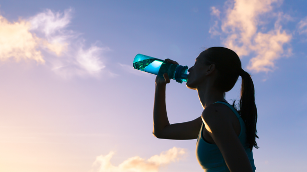 Woman drinking water with a sunset behind her